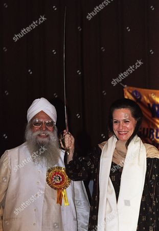 GANDHI Congress Party President Sonia Gandhi, right, holds a ceremonial sword given to her by the Sikh community in New Delhi . The Congress Party hopes to make some gains on the ruling Bharatiya Janata Party in the upcoming assembly elections on November 25. Man at left is unidentified