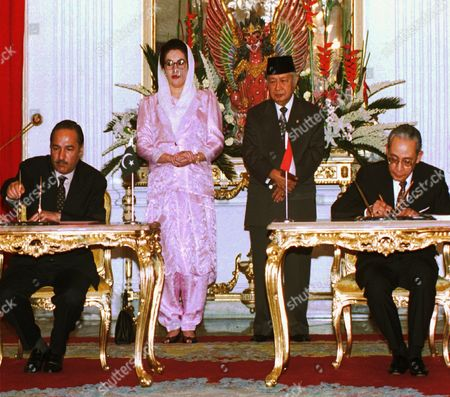SIGNING CEREMONY Pakistani Prime Minister Benazir Bhutto and Indonesian President Suharto, center, witness the signing Memorandum of Understanding between the two countries on trade and investment, by Foreign Minister Ali Alatas, right, and Pakistani Trade Minister Choudhry Ahmad Mukhtar in Jakarta