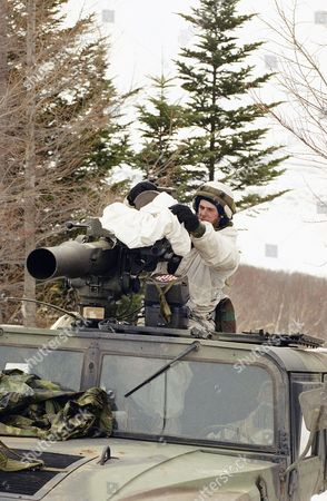 Pfc. Fred Wilson of Detroit takes a cover off the sight of a TOW anti-tank missile launcher mounted atop a HUMVEE during North Winds '92 winter military exercise in Hokkaido in Kamifurano, northern Japan on . Pfc. Wilson and his anti-tank unit were part of the 450-strong 5-9 Battalion from the 6th Light Infantry Division headquartered in Fairbanks, Alaska, taking part in the annual training with Japanese counterparts