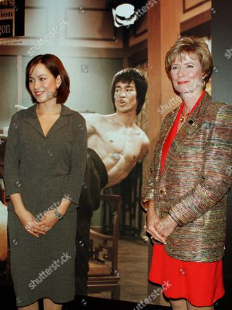 """CADWELL Actress Shannon Lee, left, and her mother Linda Lee Cadwell, daughter and wife of late martial arts actor Bruce Lee, stand in front of a photo panel showing the actor in a scene, at the opening ceremony of the """"Bruce Lee exhibition - Memory of the Dragon"""" in Tokyo to commemorate the 25th anniversary of his death. The exhibit runs from Aug. 5 to 25th"""