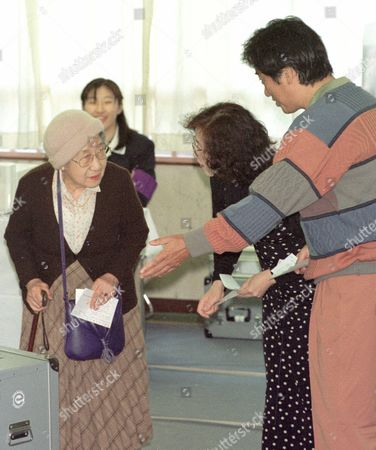 NAOTO NOBUKO KAN Naoto Kan, right, co-leader of Democratic Party, and his wife Nobuko, let an eldery voter cast her ballot ahead of them at a polling station in Tokyo . Japanese voters will select 500 members of the House of Representatives in the first election to elect their favorite party as well as a parliamentary candidate of their district