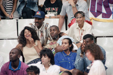 Earvin Magic Johnson, center, his wife Cookie Johnson, left, and baby Earvin Johnson III watch the USA womans basketball game, Barcelona, Spain. Above Johnson is Julius Dr. J. Erving and in the first row, left to right, Michael Jordan, his wife Juanita Jordan, David Robinson and his wife Valerie Robinson