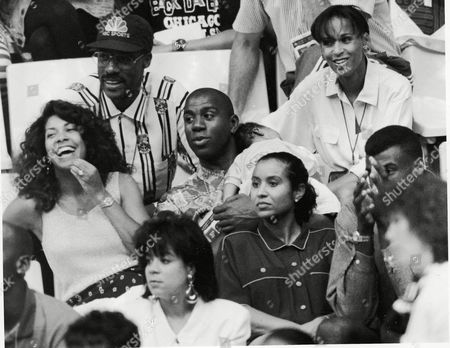 Earvin Johnson, center, his wife Cookie and baby Earvin Johnson III, center, watch the USA womens basketball game, Barcelona, Spain. Above Johnson is Julies Dr. J. Erving and in the first row are, from left to right, Michael Jordan, his wife Juanita and David Robinsons wife Valerie