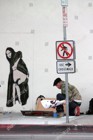 Nick Walker stenciling graffiti art titled 'Moona Lisa' on a wall