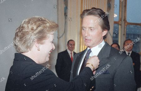 Stock Image of French Culture Minister Catherine Trautmann pins the medal of Officer in the Arts and Letters order to US actor Michael Douglas, in Paris, France. Douglas was honored by the French Government for his acting career Friday, and the culture minister described him as Hollywood as most talented golden boy