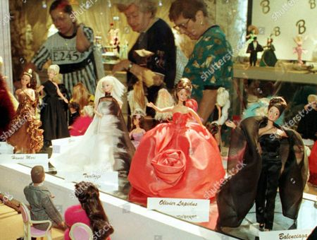 Tourists admire Barbie dolls dressed by Haute Couture fashion designers, from the left, Angelo Tarlazzi, Olivier Lapidus and Balianciaga during the Barbie's exhibition in the national museum of Monaco