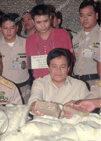 Stock Image of BARBERS TONG Interior and Local Government Secretary Robert Barbers (seated) presents to the media the more than 400 million peso (dlrs 15.4-million) worth of drugs seized from Hong Kong national Wai Kuen Alan Tong (at the back) at his rented house in Tagaytay, a resort city south of Manila. The bust, said to be one of the biggest in the country's history, yielded more than 200 kilos of metamphetamine hydrochloride, or shabu, and several blocks of pure heroin