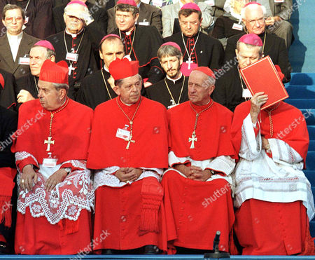 """Stock Picture of Cardinal Eduard Cassidy from the Vatican team shades face with a copy of the Pope's speech, which he gave during the closure of the inter-religion meeting """"God Humankind and People"""" in University Plaza downtown Bucharest, . Some 7,000 Romanians gathered to watch the meeting and to hear the reading of a message from Pope John Paul II"""