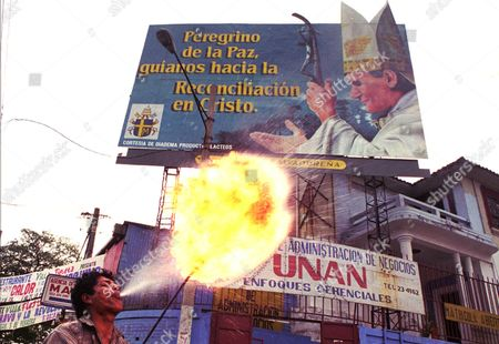 """FIRE SPITTER Juan Vicente Samayoa, 22, also known as """"El Negro,"""" spits fire below a billboard welcoming Pope John Paul II at an intersection in San Salvador, El Salvador . Various billboards have gone up around the city to welcome the Pope,who arrives February 8. The Pope will also visit Guatemala and Nicaragua"""