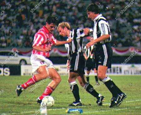 BARTON GINOLA KELIC Newcastle's Warren Barton, center, and David Ginoa, right, battle with Singapore's Ivan Kelic for control of the ball during a friendly at the National Stadium in Singapore, . The English side won 5-0
