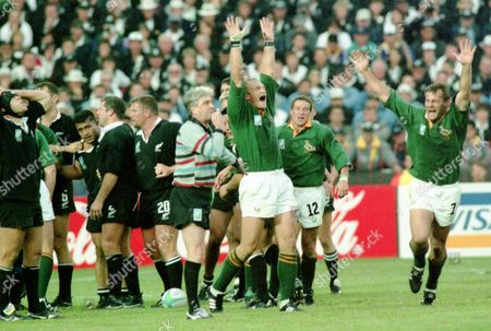 South African players celebrate as English Referee Ed Morrison, in stripes, blows for the end of extra time of the Rugby Union World Cup Final between South Africa and New Zealand at Ellis Park, Johannesburg, on . South Africa defeated New Zealand 15 - 12
