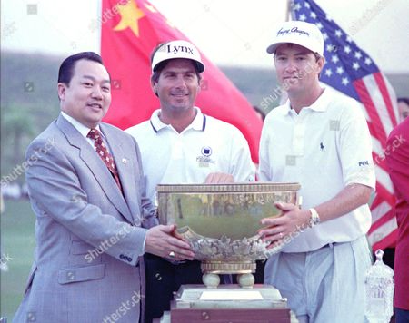 LOVE Fred Couples, center, and teamate Davis Love, right, recieve the trophy from David Chu, chairman of the Mission Hills Golf Club, after winning the 41st World Cup of Golf in the southern city of Shenzhen. Couples and Love shot a total of 33-under-par 543