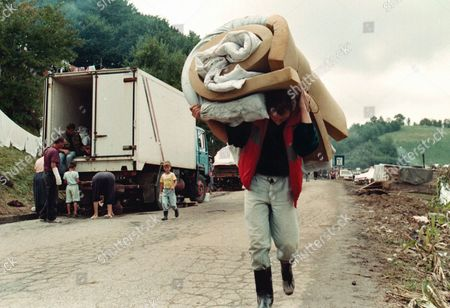 A Bosnian Muslim refugee, stuck in no-man's land in Croatia after he fled from the Bosnian Army's advance into Velika Kladusa, some 100 kms south of Zagreb, carries a bedroll towards his makeshift hut . Between 25,000 and 30,000 refugees, supporters of the Muslim rebel general Fikret Abdic, are stuck here after they fled fighting when Croatian and Bosnian forces took the Bihac pocket. Abdic led Bosnian Muslim forces who supported the Bosnian Serbs