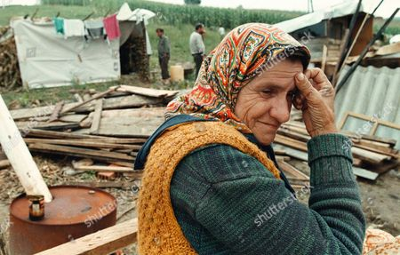 A Bosnian Muslim refugee, stuck in no-man's land in Croatia after she fled the Bosnian Army's advance into Velika Kladusa, some 100 kms (60 miles) south of Zagreb, waits on the back of a tractor as her relatives get materials together to construct a makeshift hut . Between 25,000 and 30,000 refugees, supporters of the rebel Muslim general Fikret Abdic, are stuck here after they fled fighting when Croatian and Bosnian forces took the Bihac pocket
