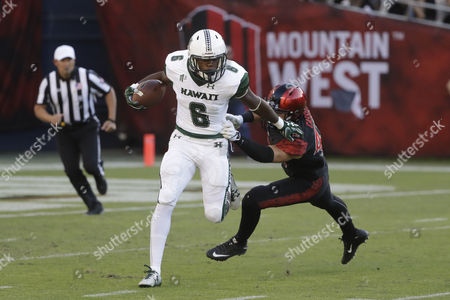 Hawaii running back Paul Harris (6) runs with the ball as San Diego State linebacker Troy Cassidy defends during the first half of an NCAA college football game, in San Diego