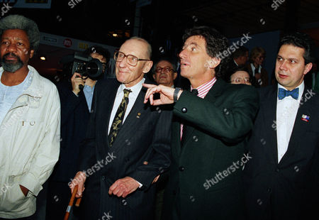 American writer William S. Burroughs, left, is led through the alleys of the 10th Paris Book Fair by French Culture Minister Jack Lang, at the opening of the show in the Grand Palais in Paris, . Burroughs was in Paris to present the first exhibition of his paintings