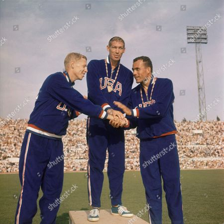 Triple handshake between the three winners of the men's 400-meter hurdles race of the Rome Summer Olympics stand on the podium for the medal ceremony at the Olympic Stadium. They are: Glenn Davis; center, winning gold medal; Clifton Cushman, Ill., left, winner of silver medal; and Richard Howard, right, who won the bronze medal