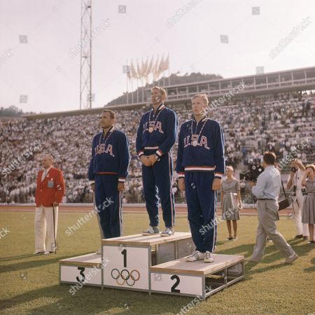 Three winners of the men's 400-meter hurdles race of the Rome Summer Olympics stand on the podium for the medal ceremony at the Olympic Stadium. They are: Glenn Davis; center, winning gold medal; Clifton Cushman, right, winner of silver medal; and Richard Howard, who won the bronze medal