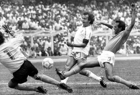 France's Michel Platini, centre, beats both Italian goalkeeper Giovanni Galli, left, and Italian defender Antonio Cabrini to the ball to score the first goal for his team during the Football World Cup second round match in Mexico City, Mexico, on