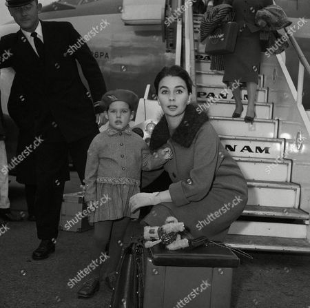 Travel weary Tracy young daughter of British Born actress Jean Simmons, lets go with a big Yawn as mother helps her into her coat at London Airport on . They had just stepped off a plane from New York. Miss Simmons is married to Stewart Granger. Both are naturalized American citizens