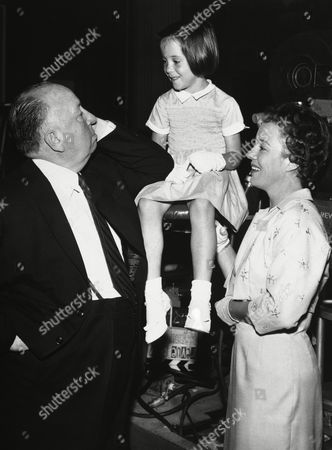 """Stock Photo of British director and producer Alfred Hitchcock presents his eldest granddaughter six-year old Mary O'Connell, who makes her acting debut, when she appears with her mother, actress Pat Hitchcock, right, in an episode of the famed """"Alfred Hitchcock presents"""" television series in America later this autumn. Pat Hitchcock is in private life, the wife of trucking executive Joseph O'Connell. Hitchcock himself, left, one of the most original directors in the film industry, has won a new fame for his handling of television"""