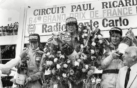 MARIO ANDRETTI U.S. racing driver Mario Andretti, center, showers photographers and cheering fans with a magnum of champagne after winning the Grand Prix de France in a Lotus MK 1V Sunday afternoon, at LeCastellet, France. At left is teammate of Andretti, Ronnie Peterson, who placed second. At right is James Hunt of Great Britain, who placed third