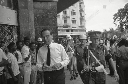 Associated Press correspondent Michael Goldsmith, 39-year-old British subject, is escorted from Leopoldville's Memling Hotel, to a waiting jeep by Indonesian and Ghanaian troops of the United Nations peace force after a squad of armed Congolese troops tried to break into his room and arrest him. The soldiers said they were acting on the orders of Col. Joseph Mobutu, the Congo strongman, who has accused Goldsmith of criticizing the behavior of Congolese troops and attacking his regime. The correspondent has been placed under U.N. protective custody