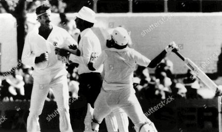 Cricket umpire Tony Crafter separates Australian fast bowler Dennis Lillee, left and Pakistan batsman Javed Miandad during a disagreement in the First Test at Perth, on