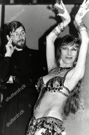 "Professional belly dancer Jill Chartwell performing at the Holy Trinity Church Hall in East Finchley, under the watchful eye of local vicar, the Reverend Lawrence Hill in London on . Jill will be giving belly dancing lessons to the ladies of Holy Trinity following an advertisement by the vicar for the use of the hall in The Stage, the theater magazine. Reverend Hill said; ""I thought an amateur playgroup might be grateful for the hall to hold rehearsals in. I never thought we would get a belly dancing club here. However, it's been fixed up and I must admit I am quite looking forward to it"