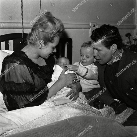 Watched over by mum and dad, 20-month-old Terry Downes, Jr., fondles his new brother, six-day-old Paul Charles, in a London nursing home, on . Dad is Terry Downes, British Middleweight boxing champion. The couple also have a daughter, Wendy, 4 and a half
