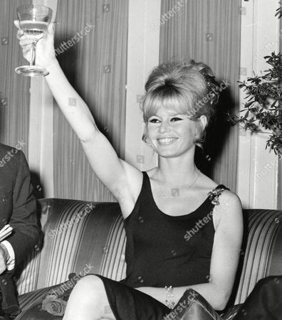 "French movie star Brigitte Bardot gives a toast during a press conference at a downtown hotel in Rome, Italy, on . Bardot is starring in a French-Italian co-production under director Jean-Luc Godard, which is based on the novel ""Il Disprezzo,"" or ""A Ghost at Noon,"" by Italian writer Alberto Moravia"