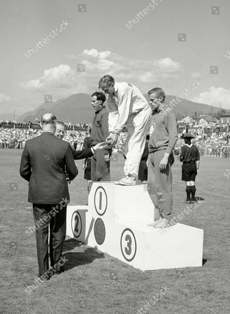 Roger Bannsiter of England stoops to receive the gold medal for winning the Mile of the Centure race at the Empire Games, now known as the Commonwealth Games, in Vancouver, Canada, on . John Landy of Australia, left, was second and Richard Ferguson of Canada, right, was third. Bannister and Landy, the only two men to ever run a mile in under four minutes