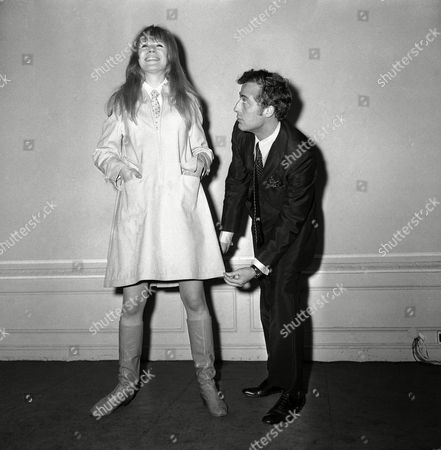 Daniel Hechter, 28-year-old French fashion designer, uses pop singer Marianne Faithfull as a model to display one of his latest creations, a short rain-dress with zip front, at the French Chamber of Commerce in London, England on