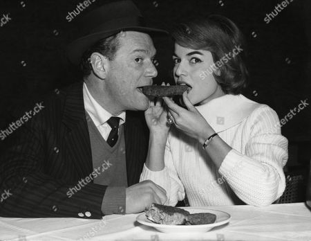 """U.S. American actor and singer Eddie Constantine, shares a hamburger with German actresses Margit Saad, at a restaurant in Hamburg, West Germany, airport, . Constantine is in Hamburg, to shoot outdoor scenes for his latest movie """"Here comes Eddie&quot"""