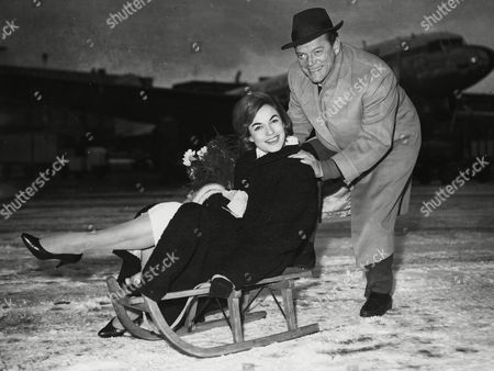 """U.S. American actor and singer Eddie Constantine, pushes German actresses Margit Saad, sitting on a wooden sled, posing on the runway of Hamburg's, airport, . Constantine is in Hamburg, west Germany, to shoot outdoor scenes for his latest movie """"Here comes Eddie&quot"""