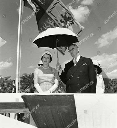 Queen Elizabeth II has her parasol held by Hugh John Fleming, premier of New Brunswick, as temperatures soared during ceremony at Queen Square in Fredericton, New Brunswick, Canada. The Queen presented certificates to over a hundred Boy Scouts, . Part of the royal standard shows behind parasol