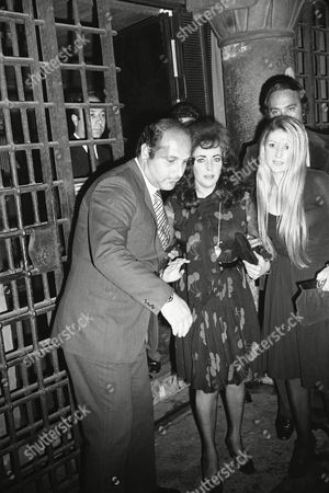 """Stock Picture of Elizabeth Taylor Liz Taylor assisted by unidentified persons, center, leaves a fashionable restaurant at dawn, Rome, Italy. Their dinner broke up in a row with several """"paparazzi"""" who were dispersed by Police after being sprayed with champagne by the Greek tycoon while the actress crouched under a table"""