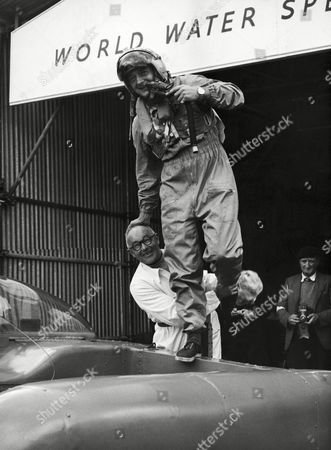 World water speed record holder Donald Campbell, in his helmet and suit, balances on one leg on his jet hydroplane Bluebird near the landing stage at Coniston Water, Lancashire on . He rests a hand on the head of Leo Villa, his chief mechanic. Campbell is at Coniston for an attempt to raise his world mark of 239 miles an hour to 250 MPH