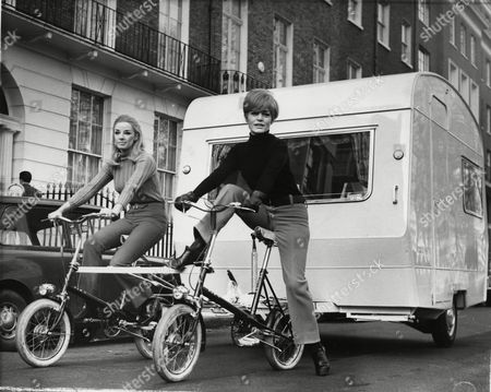 """Stock Picture of West German actress Margit Saad, right, and Miss Jean Herbert-Smith are seen riding two bicycles and towing a lightweight 10-foot-long caravan through a street in London, England, . The two bicycles were welded together side by side to form a towing unit. Margit Saad is now filming the """"Magnificent Two"""" with the British comedy team """"Morecambe and Wise"""" at Pinewood Studios, England"""