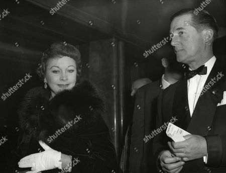 "Indian born, British actress Vivien Leigh arrives with fashion designer Hardy Amies in the foyer of the Odeon Theater at Leicester Square, London, England, to attend the premiere showing of ""The Inn Of The Sixth Happiness"". Proceeds from the film will go to found a scholarship at the Royal Academy of Dramatic Arts, as a memorial of actor Robert Donat, who died after completing his role in the film"