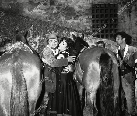 """Stock Photo of American actor Ernest Borgnine and his wife Katy Jurado embrace during scene of film """"The Brigands"""" they are shooting in Manziana, a small town 40 kilometers (25 miles) north of Rome, on . The actors, apparently reconciled in their private life, hold the leading roles of the film. Co-starring with them are the French Micheline Presle, Bernand Blier, Philippe Le Roi, and the Italians Vittorio Gassman and Rossana Schiaffino. The film is a co-production Dino De Laurentiis fair film, directed by Italy's Mario Camerini"""