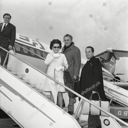"""Italian movie director Federico Fellini and his wife, actress Giulietta Masina, board a plane on at Rome's Fiumicino airport, to fly to Los Angeles where they will attend the American premiere of the director's latest film, """"Satyricon"""", Jan. 11"""