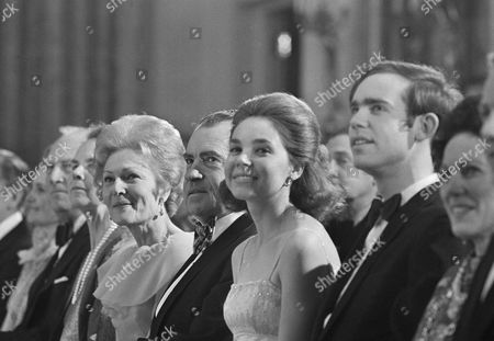 """President Richard Nixon, center, First Lady Patricia Nixon, left, and their daughter, Julie Nixon Eisenhower, second right, listen to entertainment during """"An evening at the White House,"""" held to celebrate Mrs. Nixon's birthday in Washington"""
