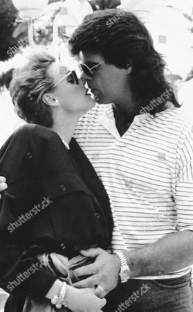 Brigitte Nielsen, gives a kiss to her friend US football player Mark Gastineau, as they showed up on the terrace of their hotel in Cannes, France, during the International Film Festival