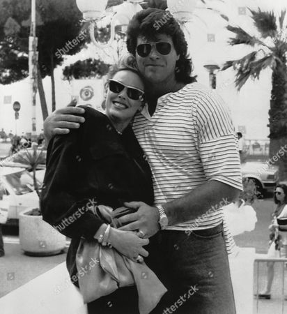 Brigitte Nielsen poses on the terrace of her hotel in Cannes, France with friend US football player Mark Gastineau during the 42nd Annual Cannes Film Festival on