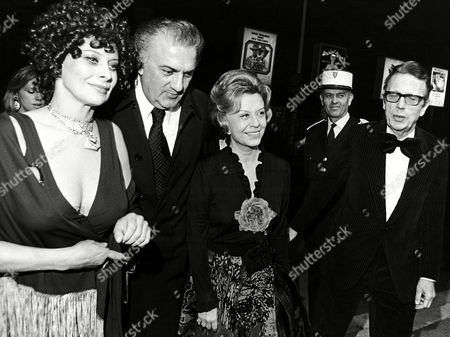 """Stock Image of Italian film director Federico Fellini with his wife Giuletta Masina, right, and French actress Magali Noel, left, is led by Robert Favre-LeBret President of the Festival (extreme right) as he arrives at the Cannes, France, Festival Palace, to attend the presentation of his film """"Amarcord"""" which opened the 27th International Film Festival"""