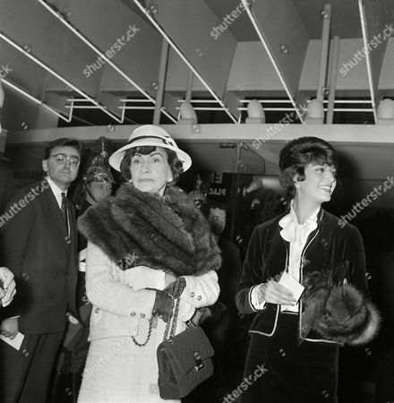 """Chanel Fashion designer Gabrielle """"Coco"""" Chanel, left, and Marie Helene Arnaud attend the gala performance of """"A Frenchman in Moscow"""" at the Kinopanorama hall at La Motte Piquet in Paris, France, . Madame Arnaud is wearing one of Chanel's velvet suits for evening wear"""