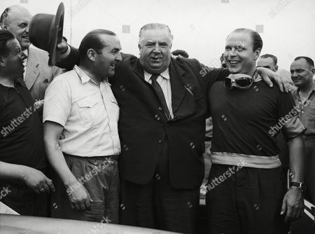 Alfred Neubauer, center, coach of the Mercedes racing team enthusiastically embraces race drivers Fritz Riess, left, and Hermann Lang, on in Le Mans, France after their win of the 24 hours race