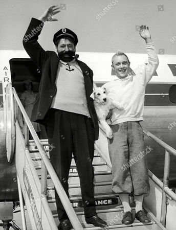 "Returning from filming ""Tintin et le mystere de la Toison d'Or"" (Tintin and the Golden Fleece) in Greece and Turkey are standing on the gangway and waving, French actors Jean-Pierre Talbot (Tintin) holding the dog Milou (Milo or Snowy), a white Fox terrier, his four-legged companion, and Georges Wilson (Captain Haddock), after their arrival on at the Orly Airport in Paris, France from Istanbul"