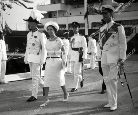 Stock Image of Britain's Queen Elizabethh II is escorted from the quay by the Governor of Gambia, Sir Edward Windley, left, after disembarking from the Royal Yacht Britannia, in Bathurst, Gambia,, for a three-day visit to Britain's oldest African colony. The Duke of Edinburgh, right, walks with the Queen. It was the last port of call in the Royal tour of West Africa